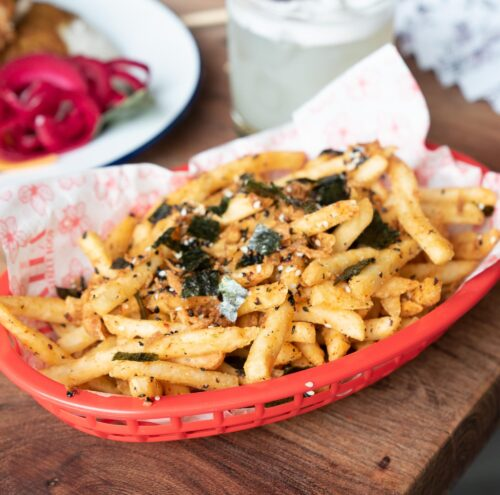 A basket of French fries tossed with seaweed, white & black sesame seeds, garlic & chilli flakes